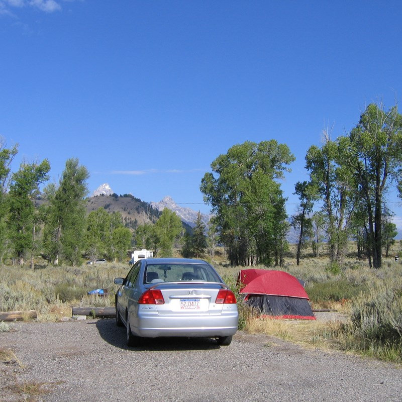 Gros Ventre campsite with red tent and silver sedan surrounded by sagebrush and cottonwoods