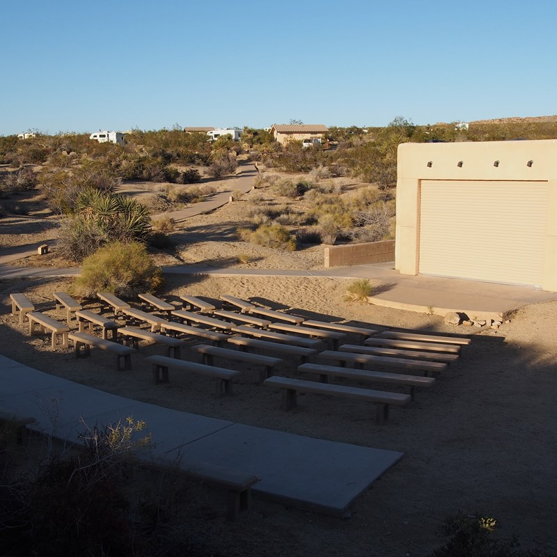 Rows of seats are in front of an outdoor stage.