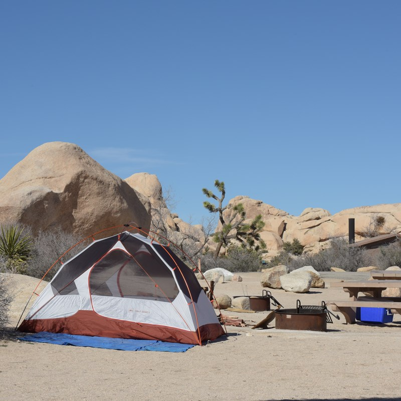A tent, fire pit, picnic table are in a campsite surrounded by boulders.