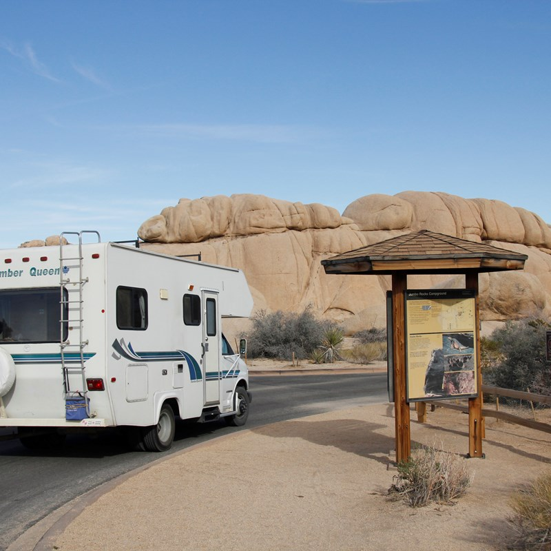 An RV drives past an campground information board.