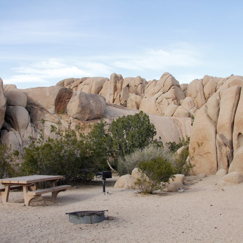 A picnic table and fire pit are in a campsite surrounded by boulders and some vegetation.