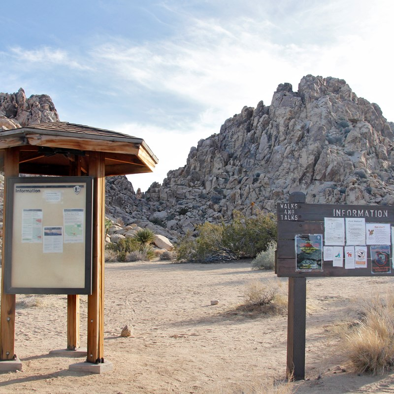 Two informational boards at the sheep pass group campground with large rocky outcrops behind them.