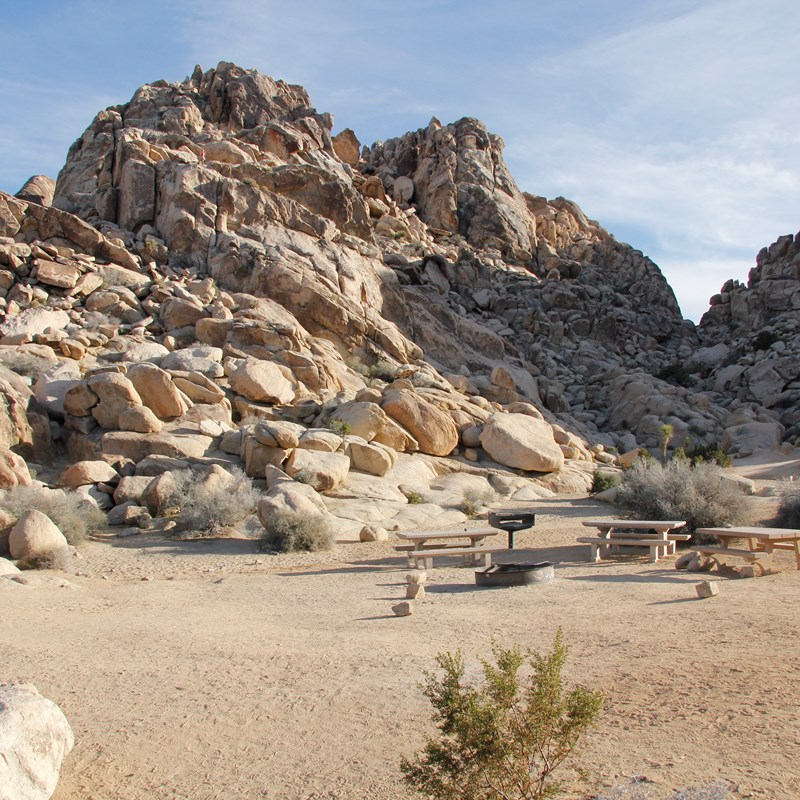 A campsite with picnic tables and surrounded by large rocky formations.