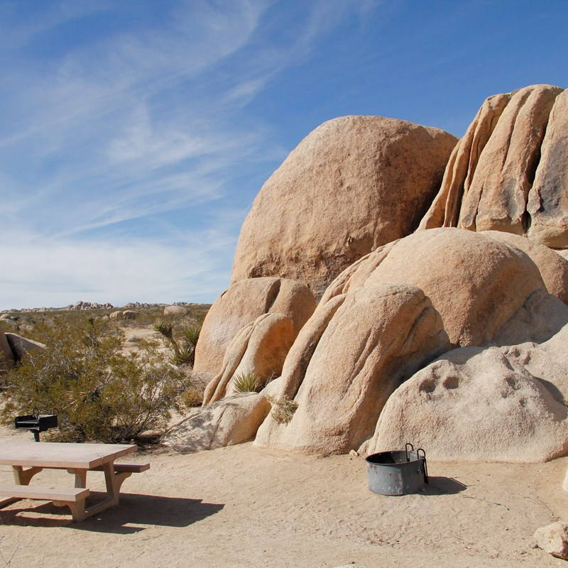 A picnic table and fire pit are in a campsite. Behind them are large boulders.