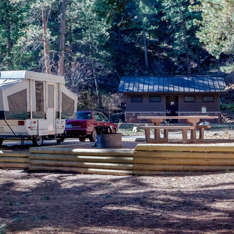 Popup camper at campsite with picnic table and comfort station