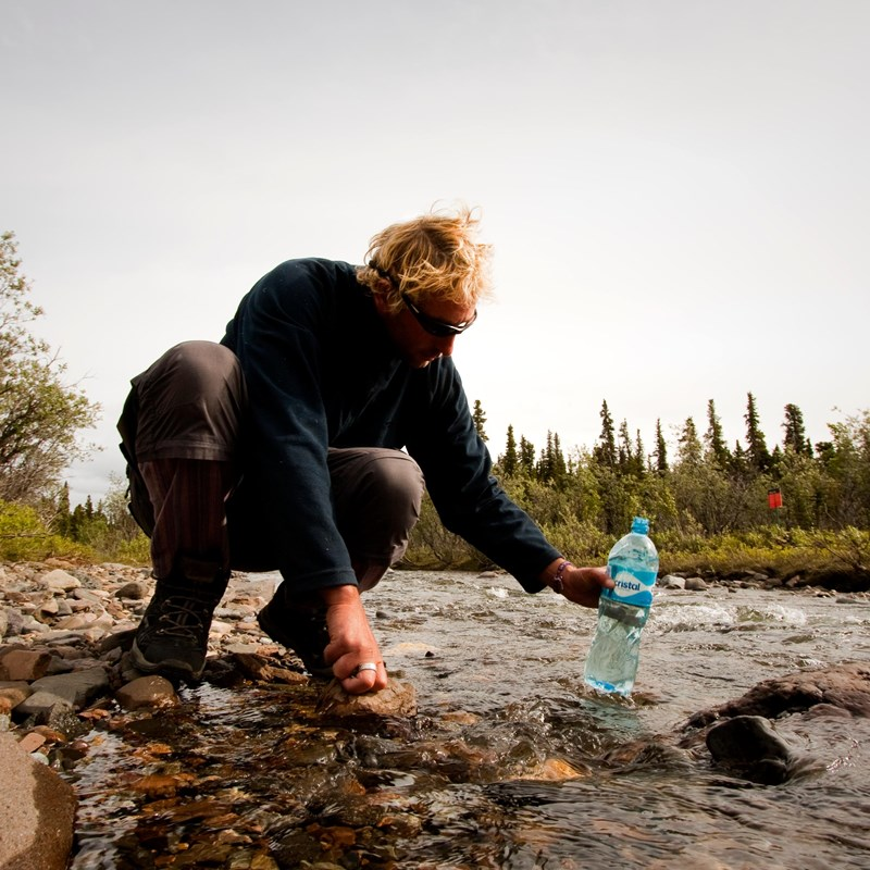 a woman filtering water into a plastic bottle from a shallow creek