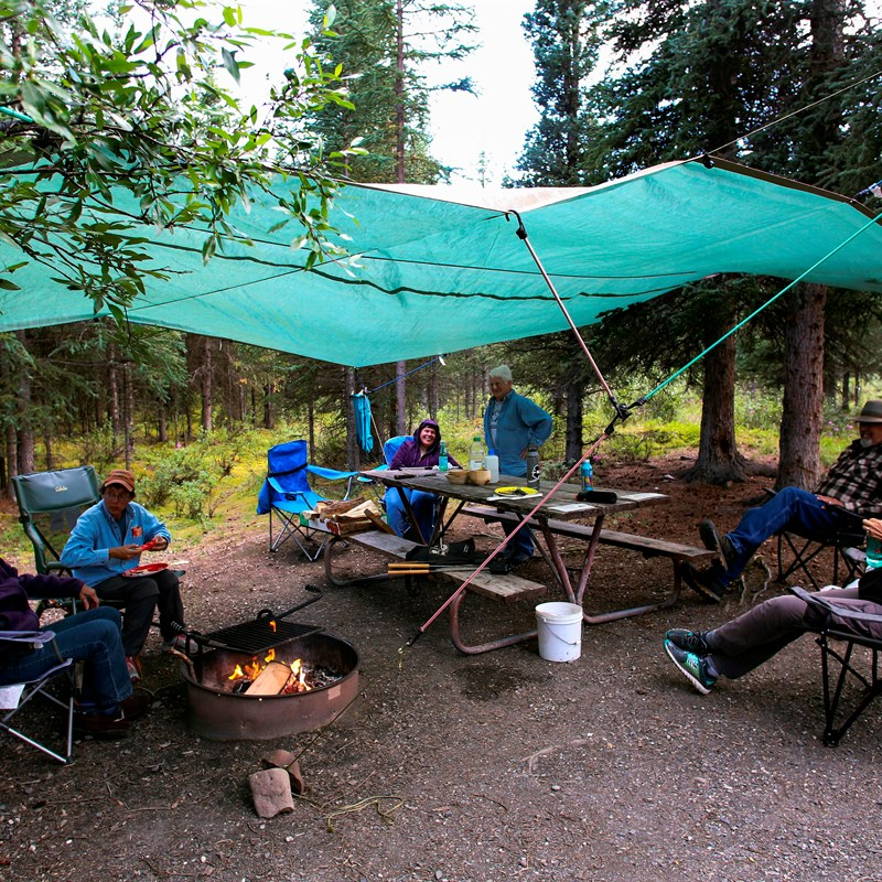 several people in camp chairs around a fire, under a tarp hung from trees