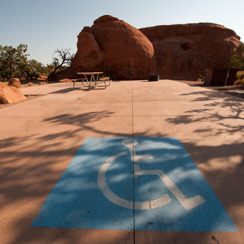a paved campsite with a large blue accessible image painted on the ground