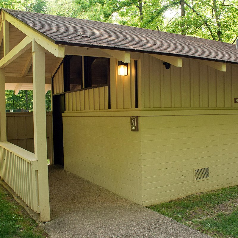 A roofed wooden restroom facility shown from outside.