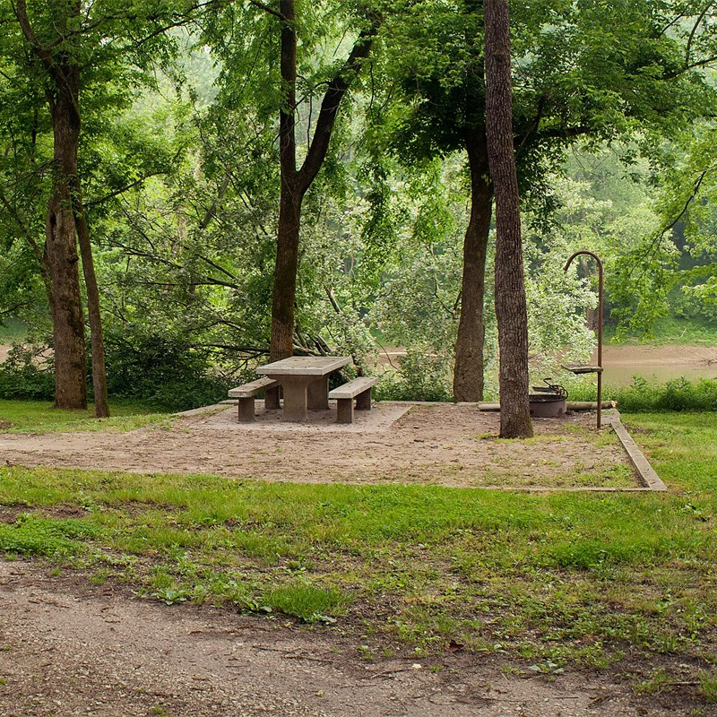 An unoccupied campsite with concrete picnic table, fire ring and lantern hook.
