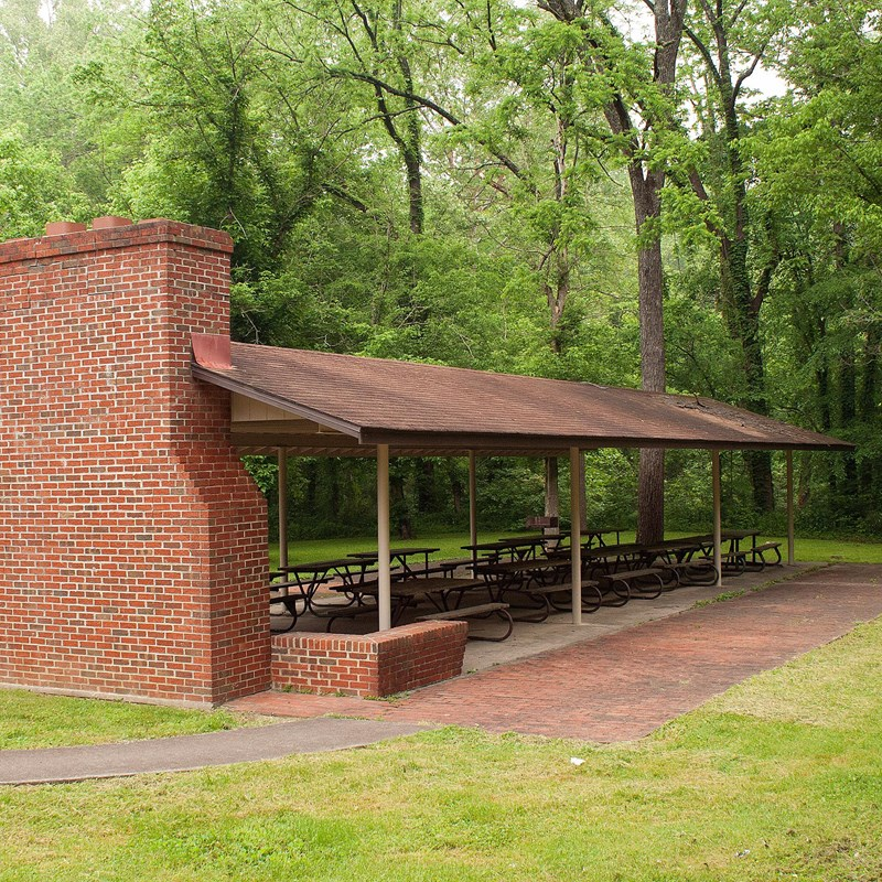An open-air picnic shelter with multiple picnic tables and a brick fireplace.
