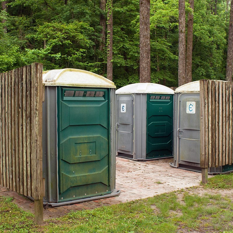 A wooden enclosure containing portable toilet facilities.