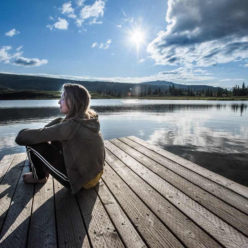 a young woman sitting on a dock sticking out into a lake