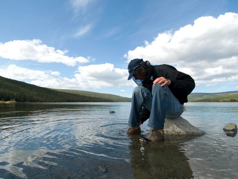 a man sitting on a rock in a lake wearing long pants, a jacket and a head net