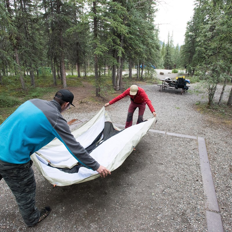 two people spreading a tent out on a gravel pad