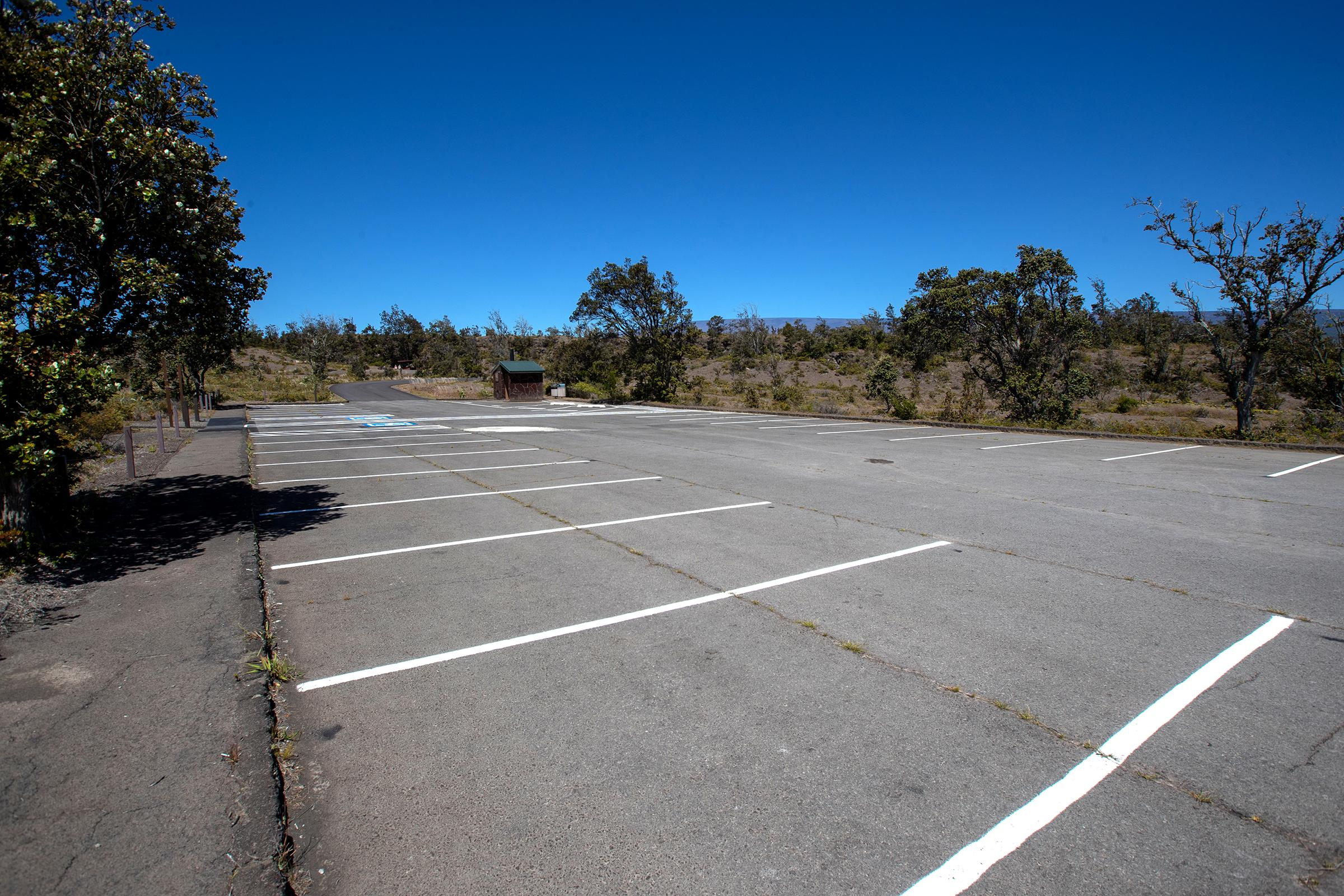 An empty parking lot with trees on  the periphery
