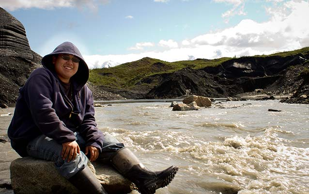 Native Alaskan youth sitting near a river