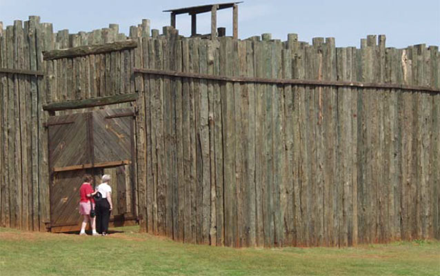 Visitors stand next to large wooden gate