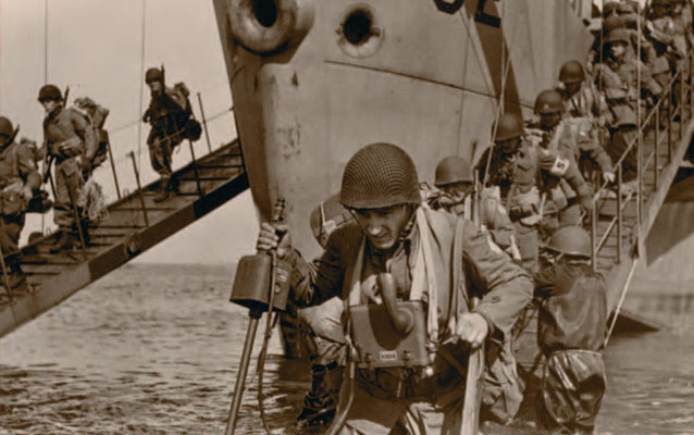 Uniformed soldiers disembarking from a vessel, onto the shore