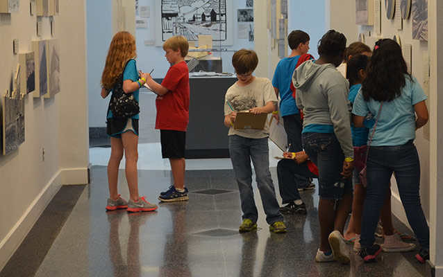 Students work on an activity in the museum hallway.