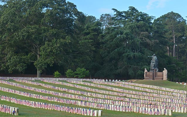 Thousands of graves are arranged in long rows, decorated with American flags.