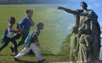 Children walking the prison site and image of a cemetery monument