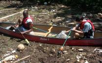 Two paddlers in the midst of trash on the river. Where does it end?