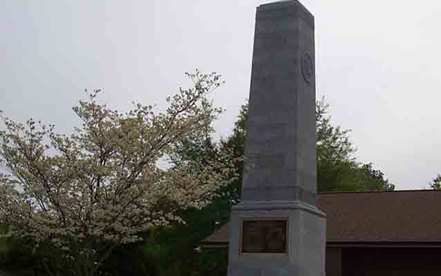 A dogwood tree blooms in front of the US Monument at the Cowpens National Battlefield Visitor Center