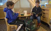 two children sitting at a small table holding books, a green backpack on the floor nearby