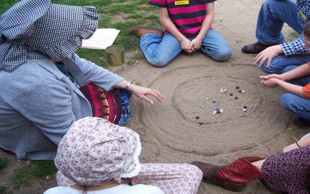 Students engage in a game of marbles.