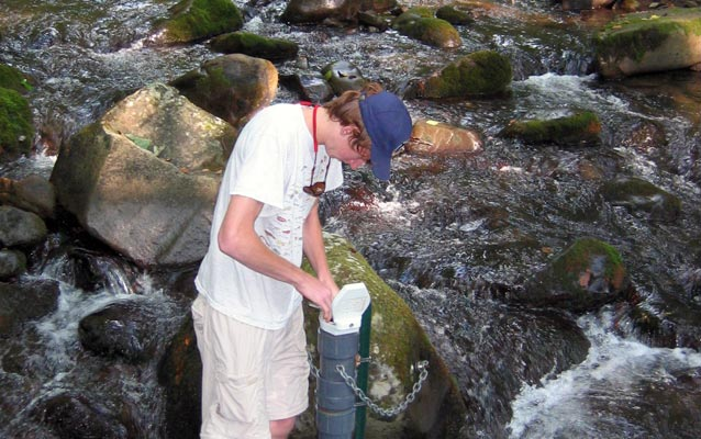 A student checking a water quality monitoring station in the middle of a stream