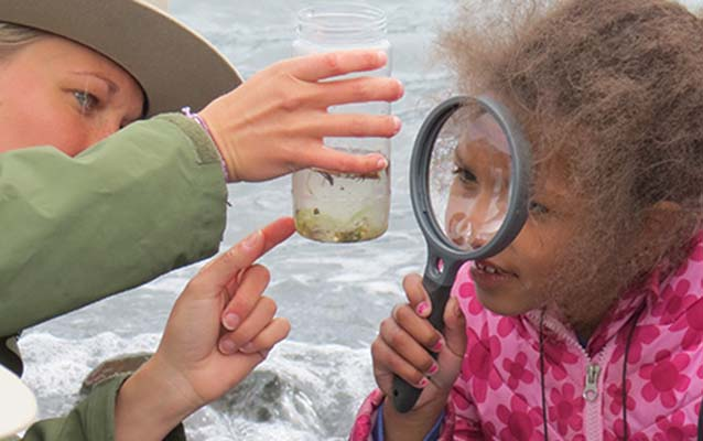 A Park Ranger shows a plankton sample to a child with a magnifying glass.