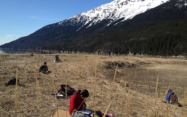 Students sit in a brown field near the ocean, with a steep mountain, partly covered in snow, rising in the background