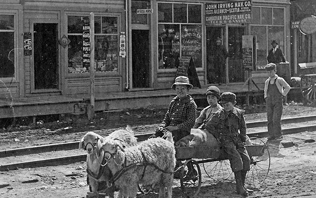 historic image of woman and two children riding a cart pulled by two goats down a dirt road, clapboard buildings in background