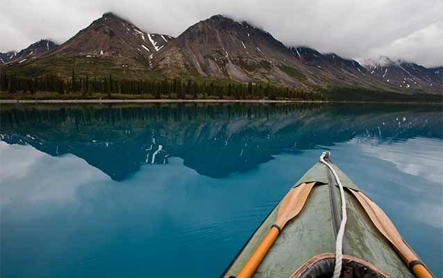 front end of a kayak in a blue lake, looking out toward cloud-covered mountains