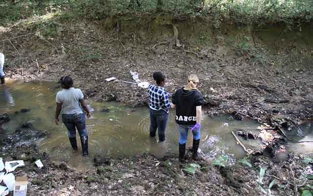 Three students standing in a stream with stream kit equipment