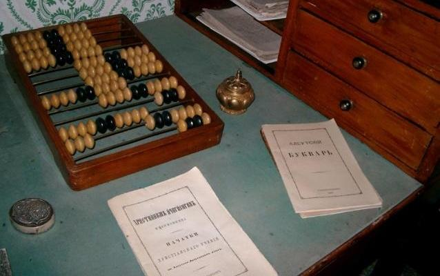 A desktop with a wooden Russian abacus, two metal ink wells, and two pamphlets in Russian.