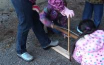 Two young girls try to start a fire using a fire bow, while two others look on.