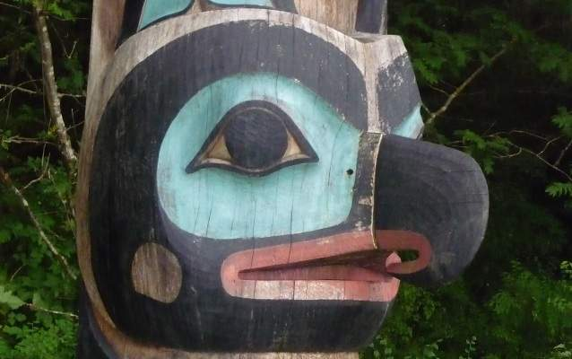 A close up picture of an eagle figure on a totem pole, painted blue, black and red.