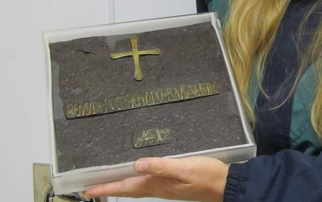 A woman holds the Russian Possession Plaque, an old square piece of metal with brass cross and Russian writing.