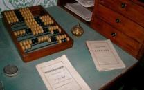 A desktop with a wooden Russian abacus, two metal ink wells and two paper pamphlets in Russian