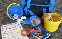 Backpack with its contents of a magnifying glass, plastic buckets, creature identification sheet, and sand shovels.