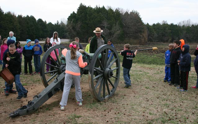 Students pretend to load a Civil War cannon.