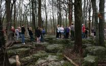 Students stand among rocky outcroppings listening to a park ranger.