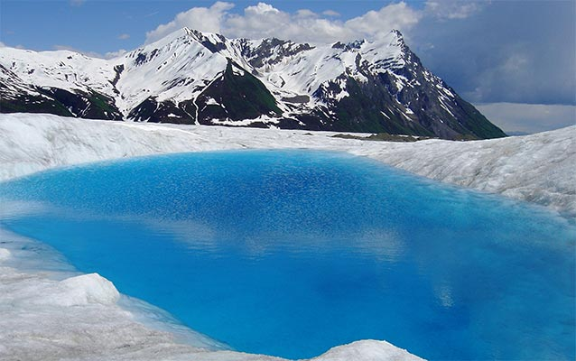 brilliantly blue pool of water surrounded by ice, a snowy mountain in the distance