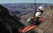 A ranger lowers herself and rescue equipment by rope into Grand Canyon.