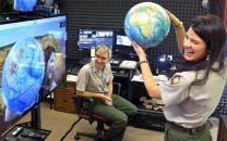 Ranger holding a globe and talking to a class during a distance learning program.