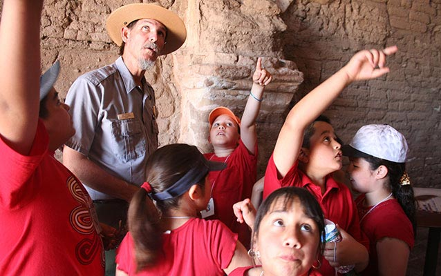 students and ranger inside adobe church pointing at clues