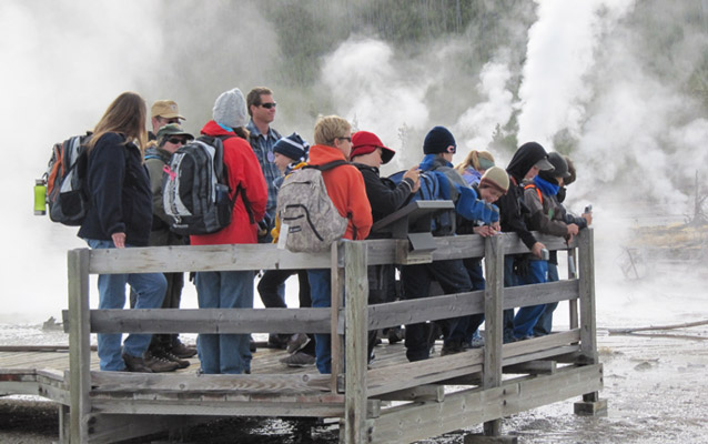 A school group and ranger near a thermal feature with steam in background