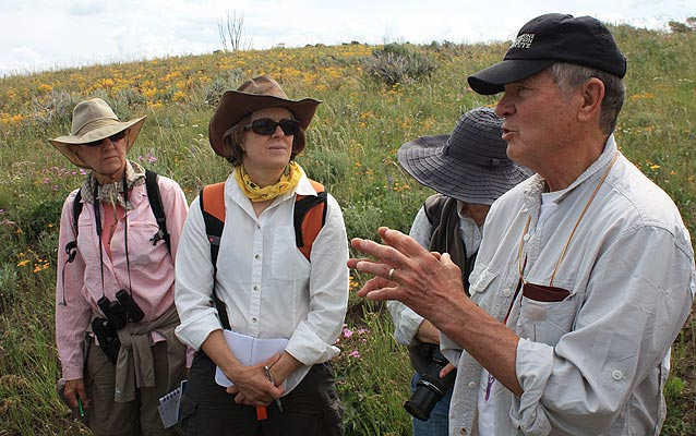 Author and botanist Wayne Phillips speaks to three people in a alpine wildflower class.